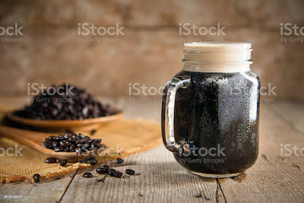 Dark rich beautiful froth foam nitro black coffee jar java stock photo