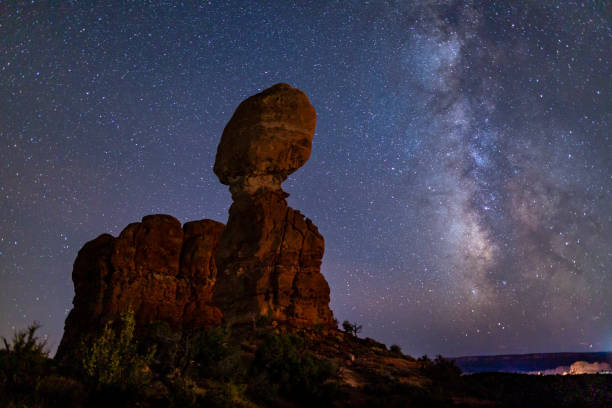 Dark Rocks and Bright Mily Way Iconic Balanced Rock silhouetted against a star-filled Milky Way in Arches National Park in Moab, Utah. arches national park stock pictures, royalty-free photos & images