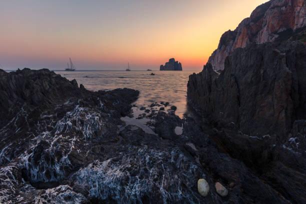 Dark Rocks of Porto Flavia stock photo