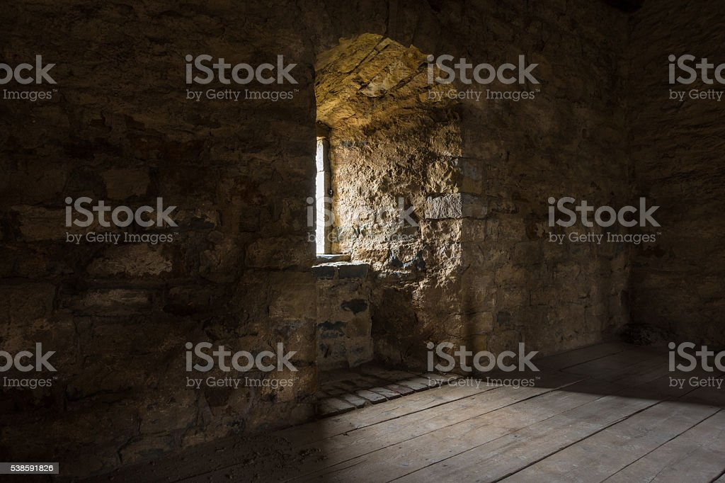 Dark room with stone walls window and wooden staircase stock photo