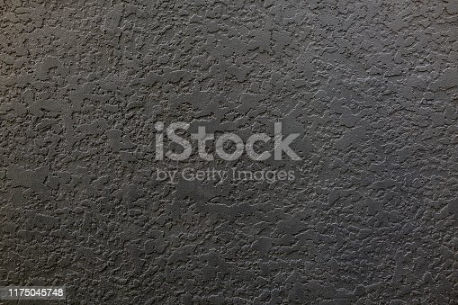Close-up of a patterned black surface of rendered wall.