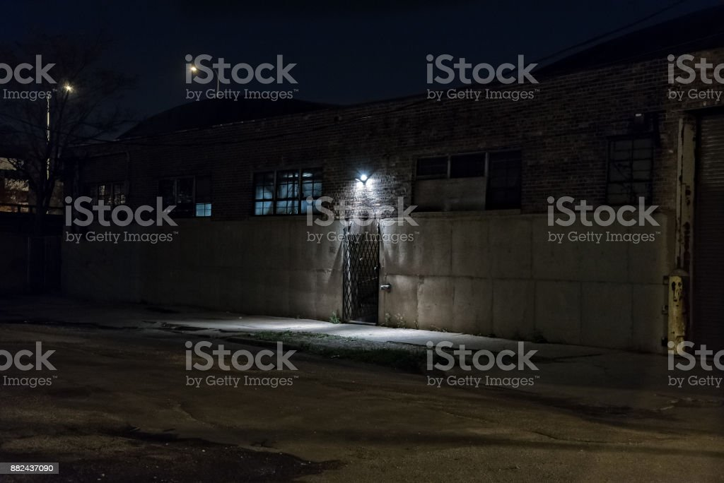 Dark scary alley at night with gated door warehouse entrance. stock photo