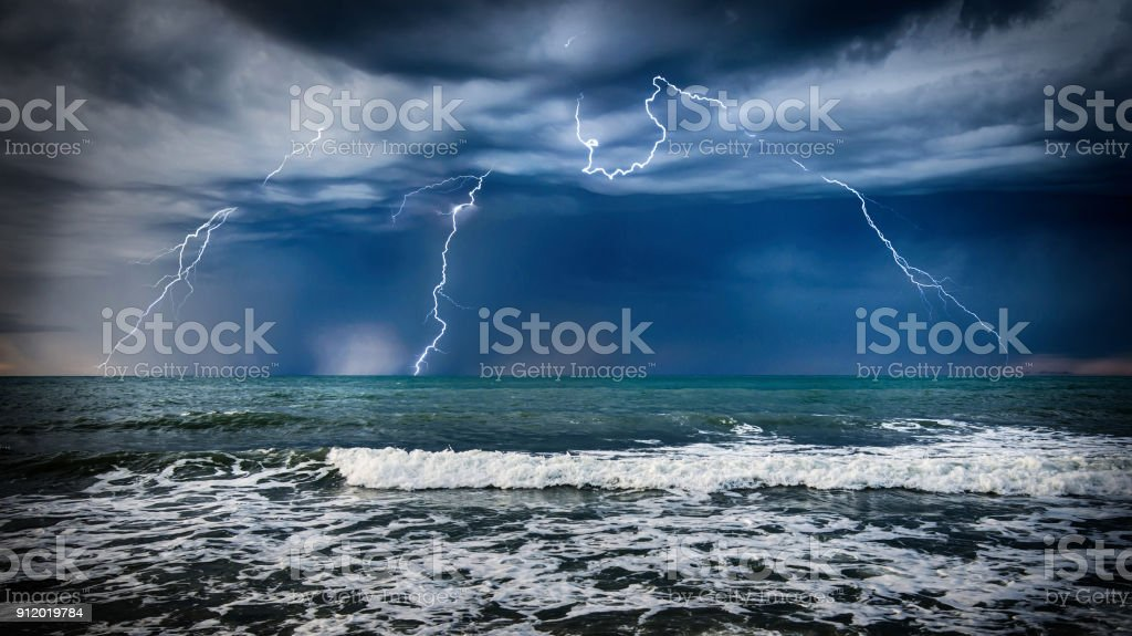 Dark sea storm with lgihting and waves at night.