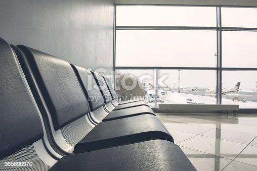 istock Dark seats locating opposite wide large window 955690970