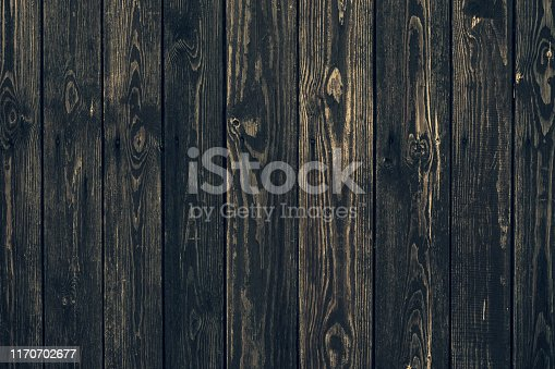 Dark shabby wooden fence with nails. Texture of black planks. Old wood brown boards. Vintage timber background. Natural pattern of hurdwood