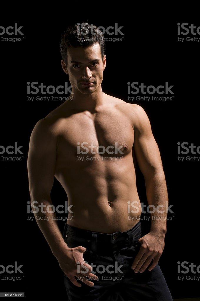 Dark shadowed photo shoot of topless man royalty-free stock photo