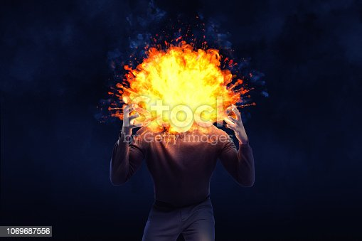 istock A dark shape of an angry man with an exploding head on a black background. 1069687556