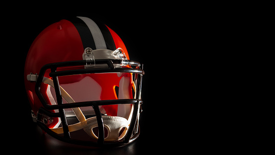 Dark side of college sports concept with high contrast lighting on American football helmet illuminated by dramatic hard light with harsh shadows isolated on black background with copy space