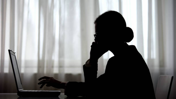 dark silhouette of businesswoman talking on phone at night making note on laptop - shifts call centre foto e immagini stock