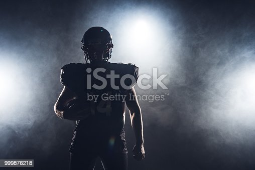 istock dark silhouette of equipped american football player with ball against white smoke 999876218