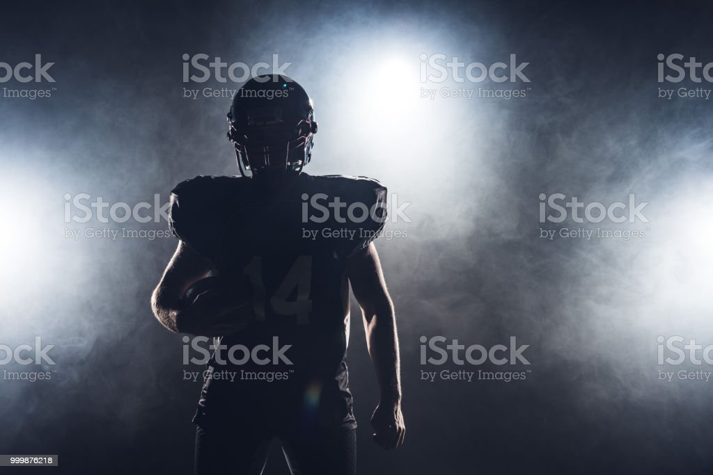 dark silhouette of equipped american football player with ball against white smoke stock photo