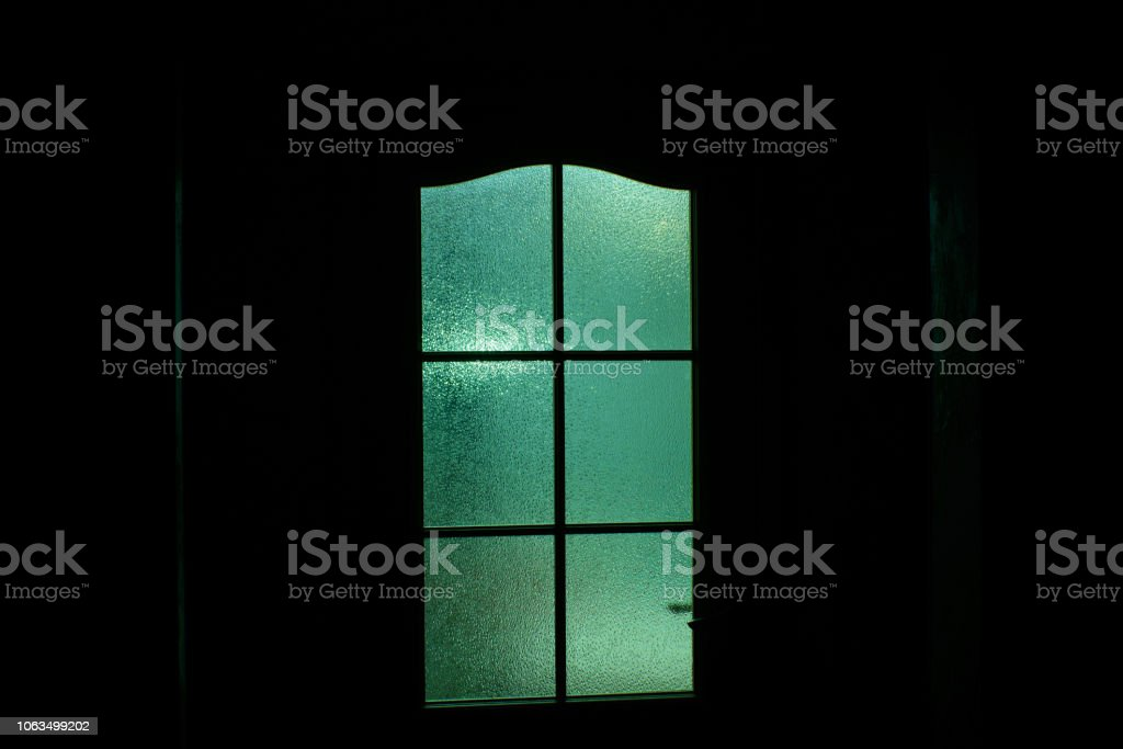Dark silhouette of glass door in supernatural green light. Locked alone in room behind door on Halloween. Nightmare with aliens, monsters and ghosts. Evil in home. Inside haunted house. Alone in dark. stock photo