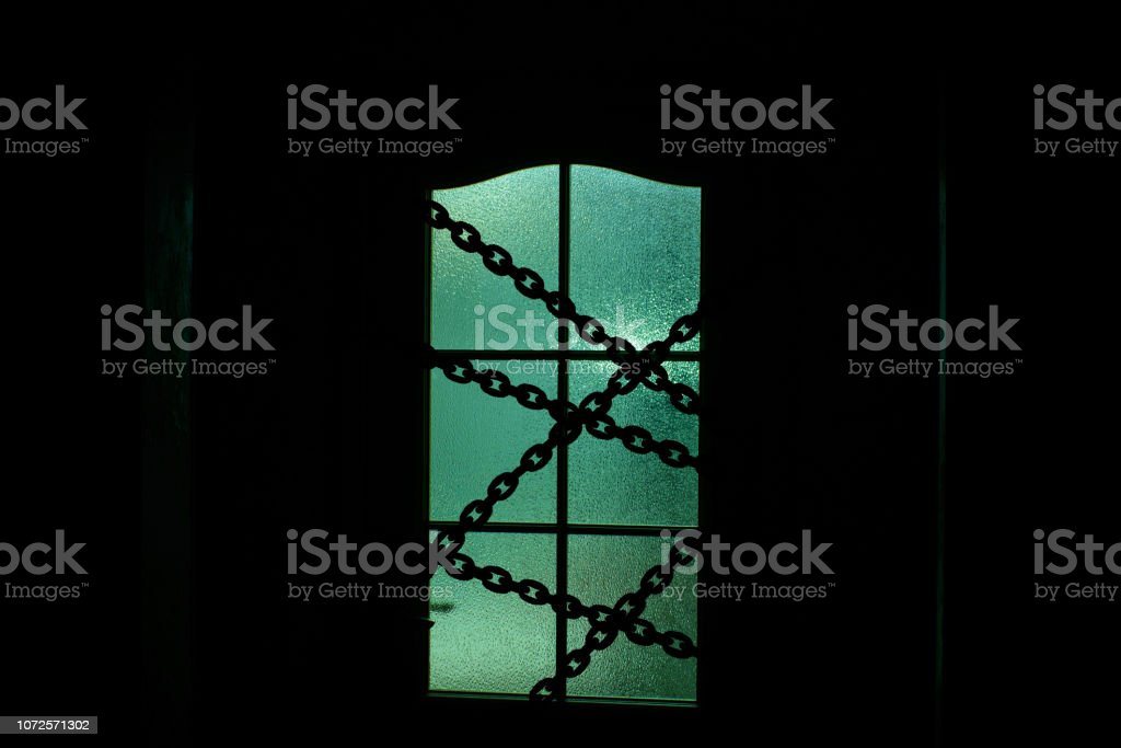 Dark silhouette of glass door with chain in supernatural green light. Locked on chain alone in room behind door on Halloween. Night kidnapping. Evil in home. Inside haunted house. Alone in dark. stock photo
