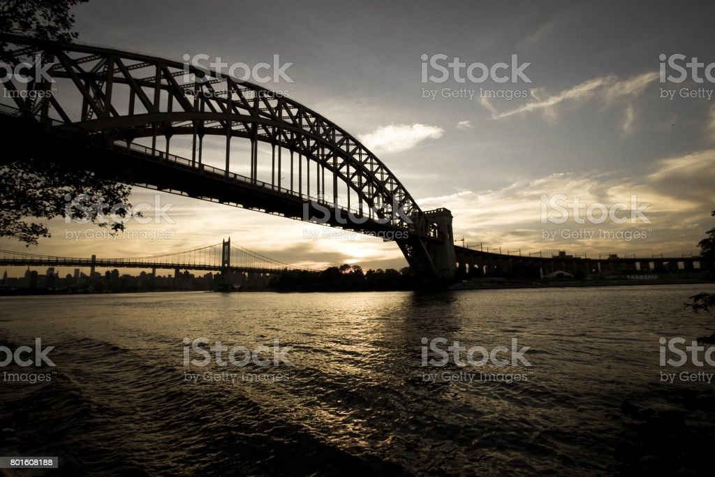 Dark Silhouette of Hell Gate Bridge and Triborough bridge over the river in vintage style, New York stock photo