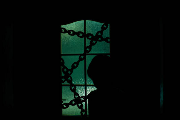 Dark silhouette of kid behind glass door with chain in supernatural green light. Locked alone in room behind door on chain on Halloween. Night kidnapping. Evil in home. Inside haunted house. stock photo