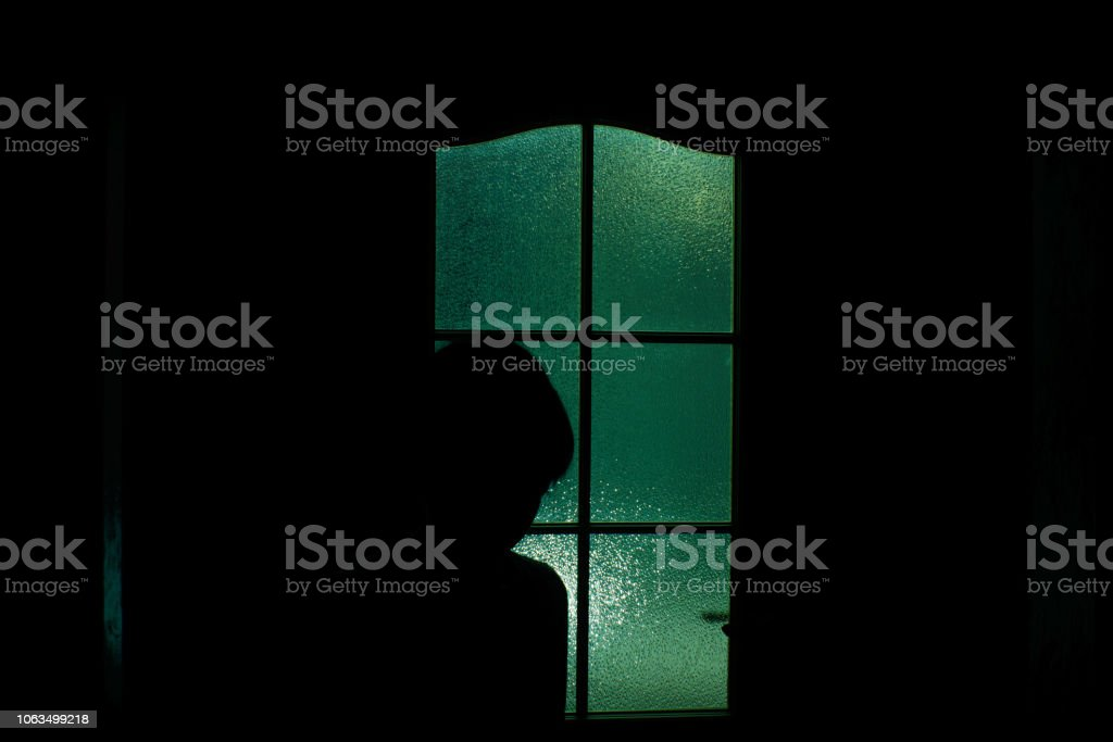 Dark silhouette of kid behind glass in supernatural green light. Locked alone in room behind door on Halloween. Nightmare of child with aliens, monsters and ghosts. Evil in home. Inside haunted house. stock photo
