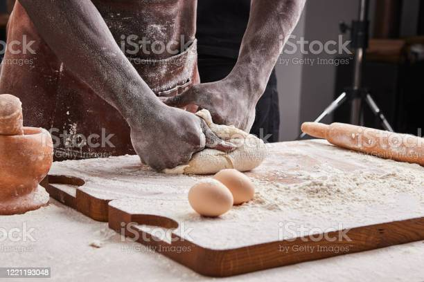 Dark skin baker man kneads dough in the kitchen pastry chef prepares picture id1221193048?b=1&k=6&m=1221193048&s=612x612&h=fzlh93h0zyqmm a3gkpiifkufvha9kfytjma2enpi0e=