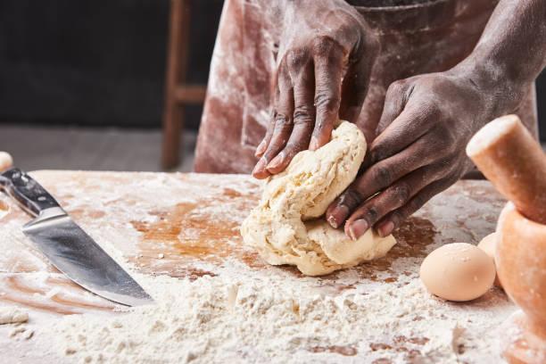 Dark skin baker man kneads dough in the kitchen pastry chef prepares picture id1221193115?b=1&k=6&m=1221193115&s=612x612&w=0&h=zvng2wfrl4krlgwv27lwk qgrtxtum9wsl7dpjn0mve=