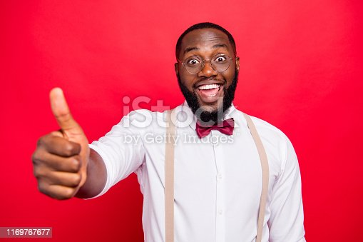 istock Dark skin manager guy raising thumb up recommending good product wear specs white shirt isolated red background 1169767677