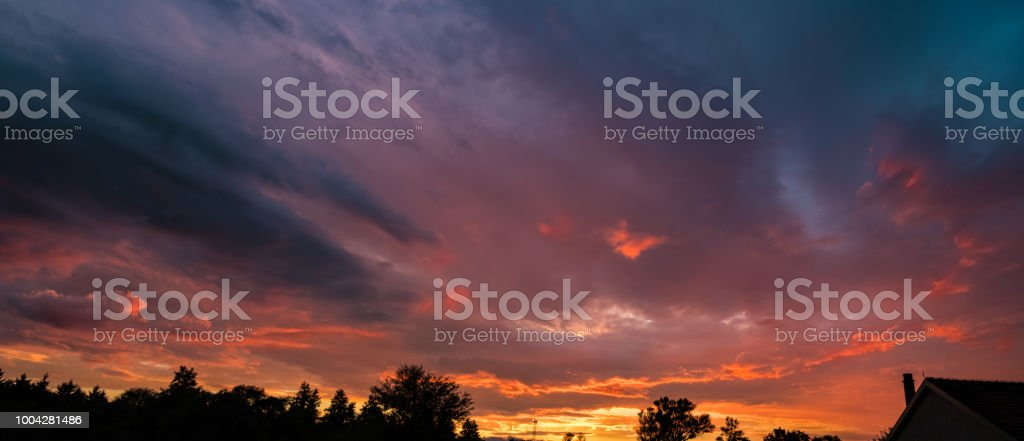 Dark sky panorama with fire colored clouds stock photo