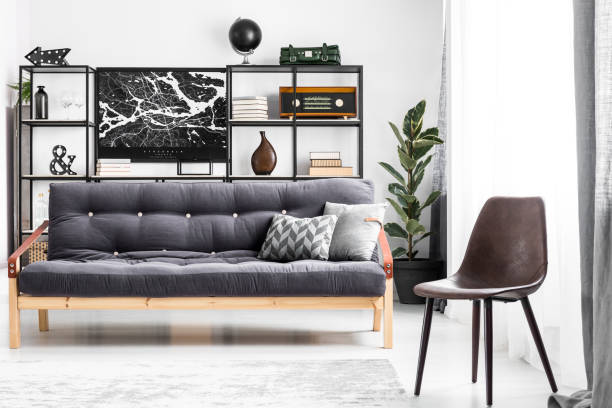 dunklen sofa im zimmer - ledersessel braun stock-fotos und bilder