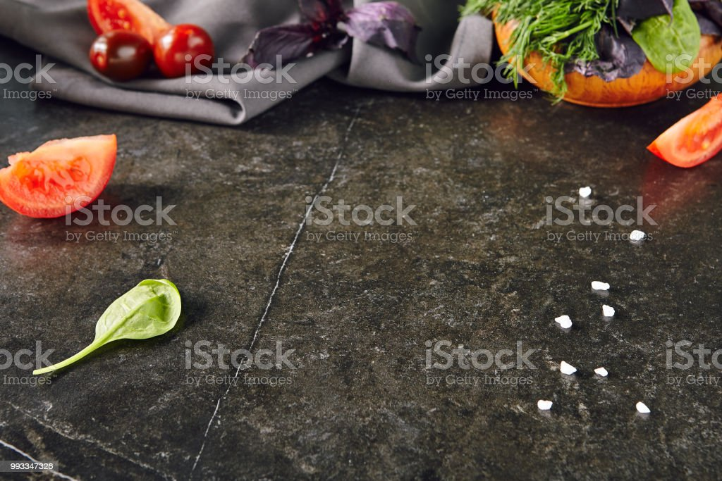 Dark Stone Background with a Bunch of Green and Purple Basil in...
