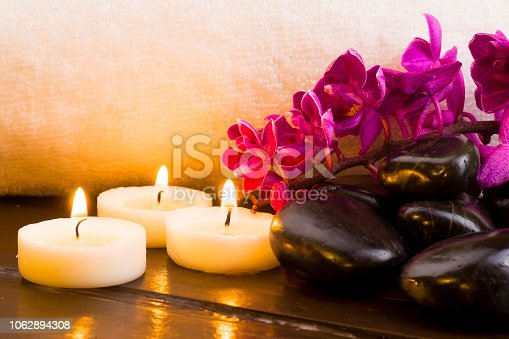 Dark stones and lighted candle and orchid on a white towel background
