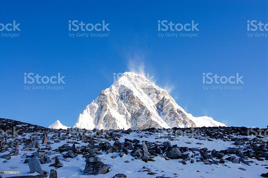 Dark stones, white Mount Pumori, blue sky stock photo