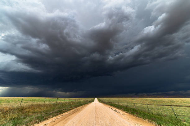 dark storm clouds over a dirt road - cielo minaccioso foto e immagini stock