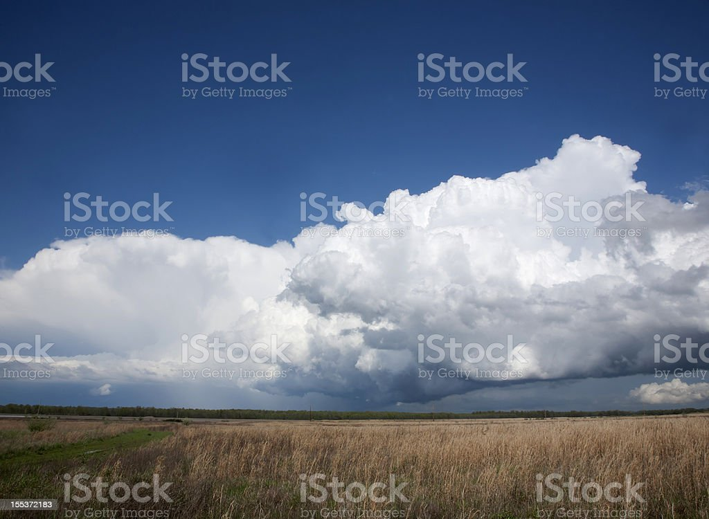 Dark storm clouds over field royalty-free stock photo