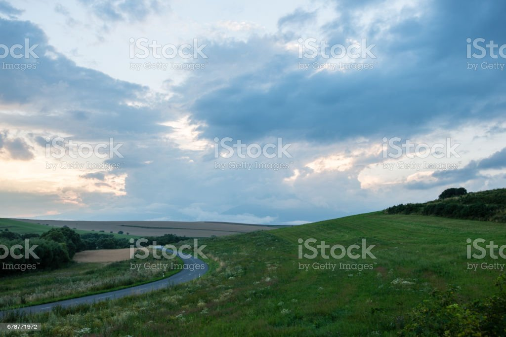 Dark storm clouds over meadow with green grass photo libre de droits