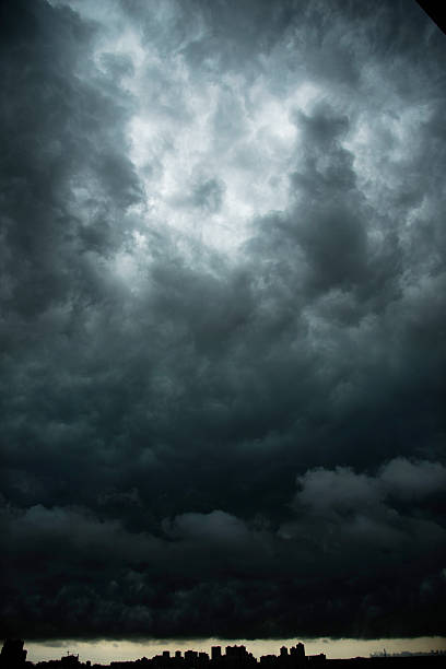 dark stormy clouds over city - atmospheric mood stock photos and pictures
