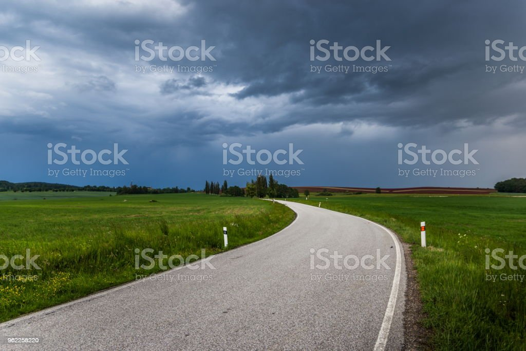 Dark stormy clouds over rural road at summer. Storm over countryside.