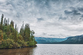 Dark stormy clouds under lake and forest. Dramatic landscape
