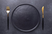 istock Dark table setting. Empty black ceramic plate, knife and fork on stone background 1223334575