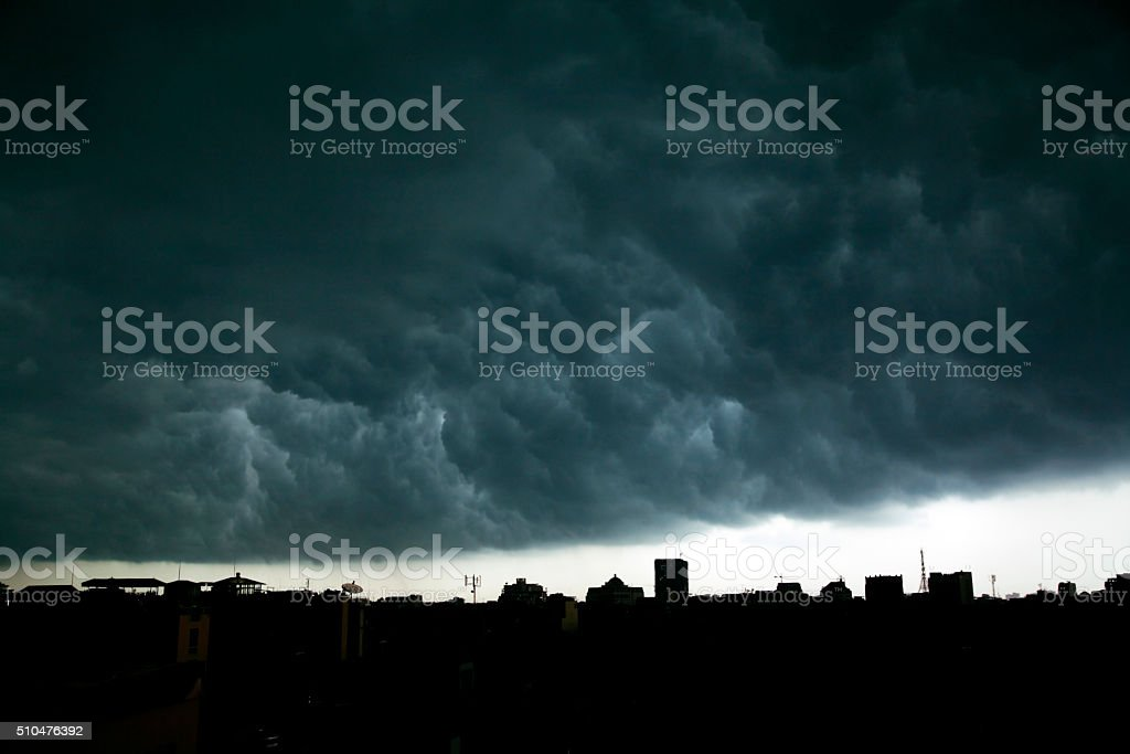 Dark, threatening storm clouds surge over city rooftops stock photo
