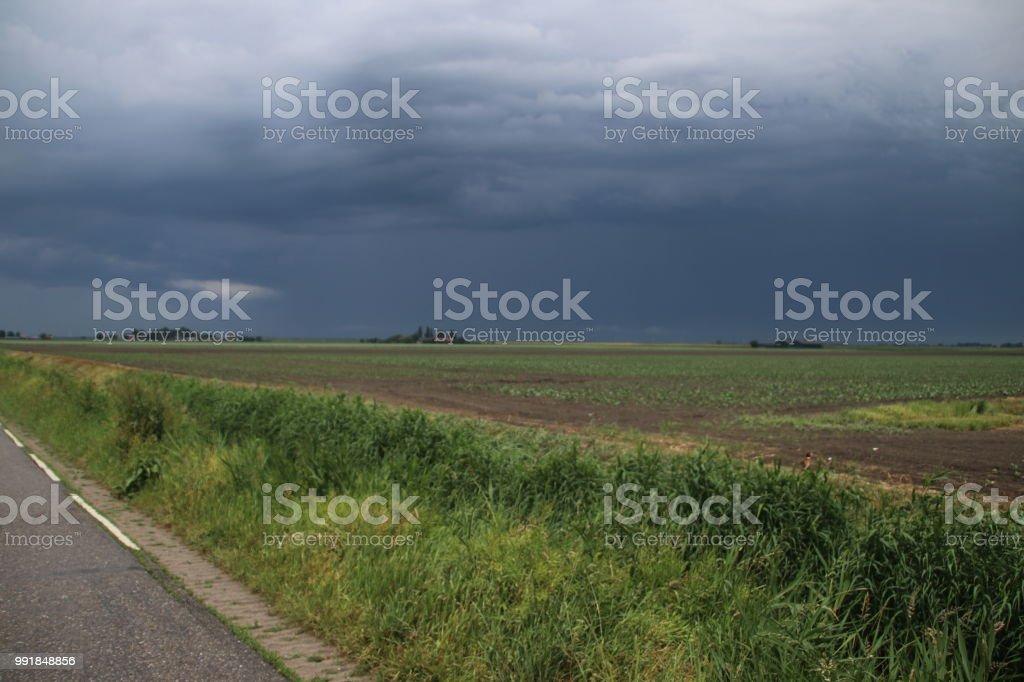 Donkere regen wolken boven polder Wilde Veenen in Waddinxveen in Nederland foto
