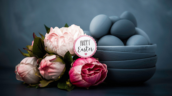 Dark toned Easter still life with peony bouquet and hand painted ombre eggs and bowls.