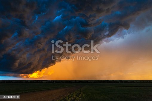 Dark, turbulent, stormy sky with rain curtain at sunset in South Dakota