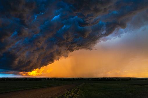 Dark, turbulent, stormy sky with rain curtain at sunset in South Dakota