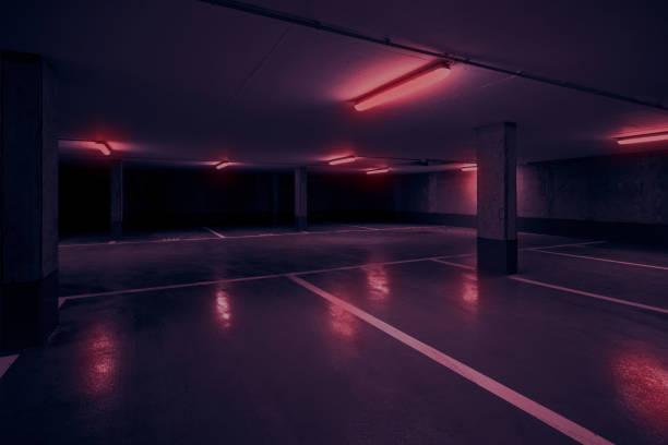 dunkle Tiefgarage unter dem Parkdeck mit roten Neonlicht- – Foto