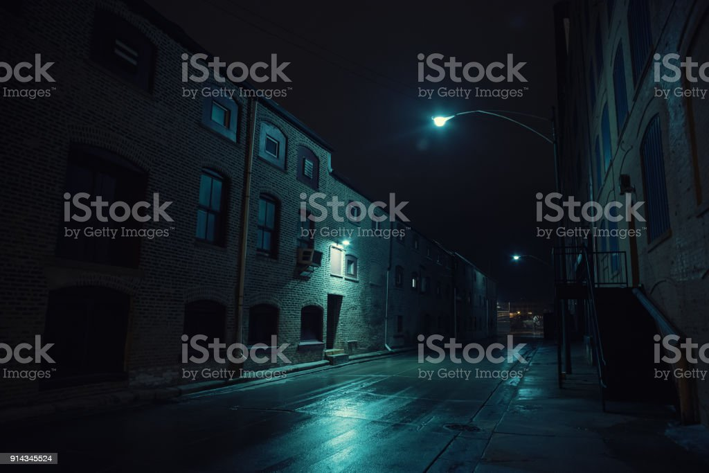 Dark urban city alley at night after a rain featuring vintage warehouses. stock photo