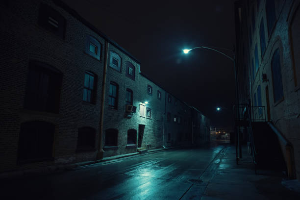 Dark urban city alley at night after a rain featuring vintage warehouses. Dark urban city alley at night after a rain featuring vintage warehouses. derelict stock pictures, royalty-free photos & images