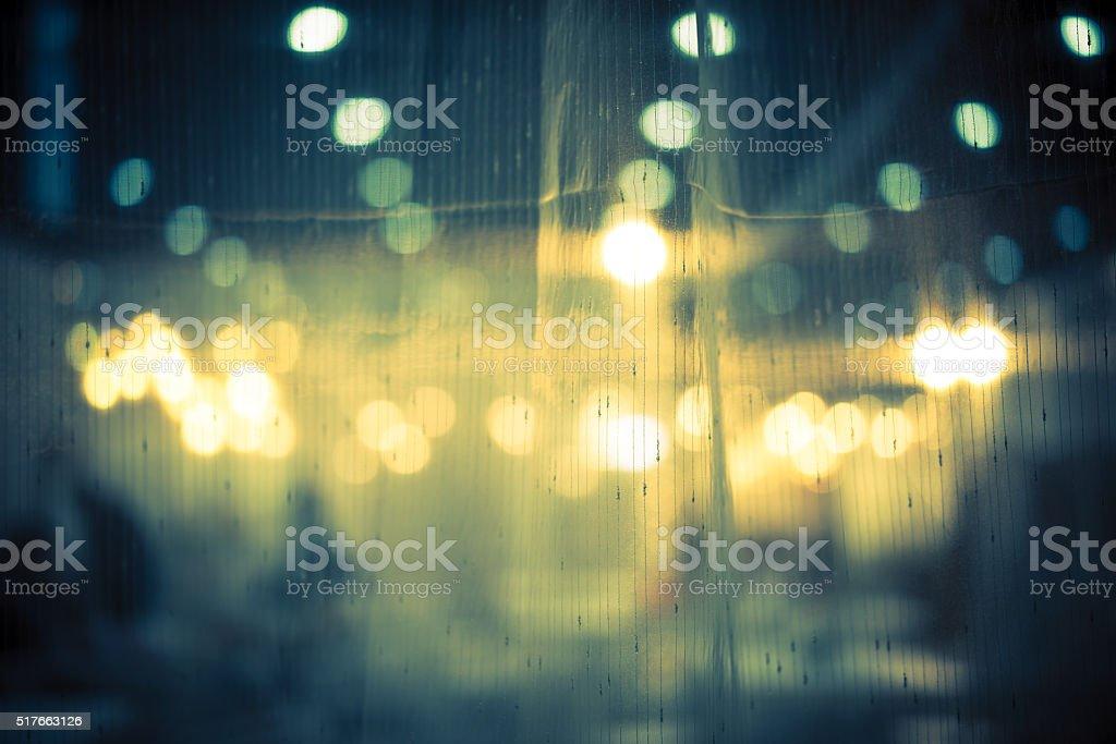 Dark vintage abstract background of night bokeh through light curtain stock photo
