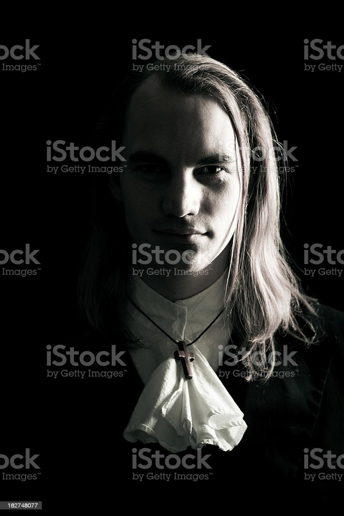 Dark Vintage Preacher Portrait A stock photo of a handsome young preacher in vintage dress with wooden crucifix shot in high contrast moody lighting on a black background. Adult Stock Photo