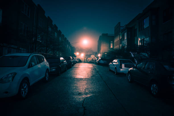 Dark wet city street with cars at night with fog. stock photo