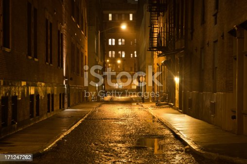 A lonely cobblestone street on a wet rainy night in New York City.
