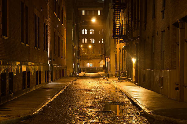 Dark wet street A lonely cobblestone street on a wet rainy night in New York City.  alley stock pictures, royalty-free photos & images