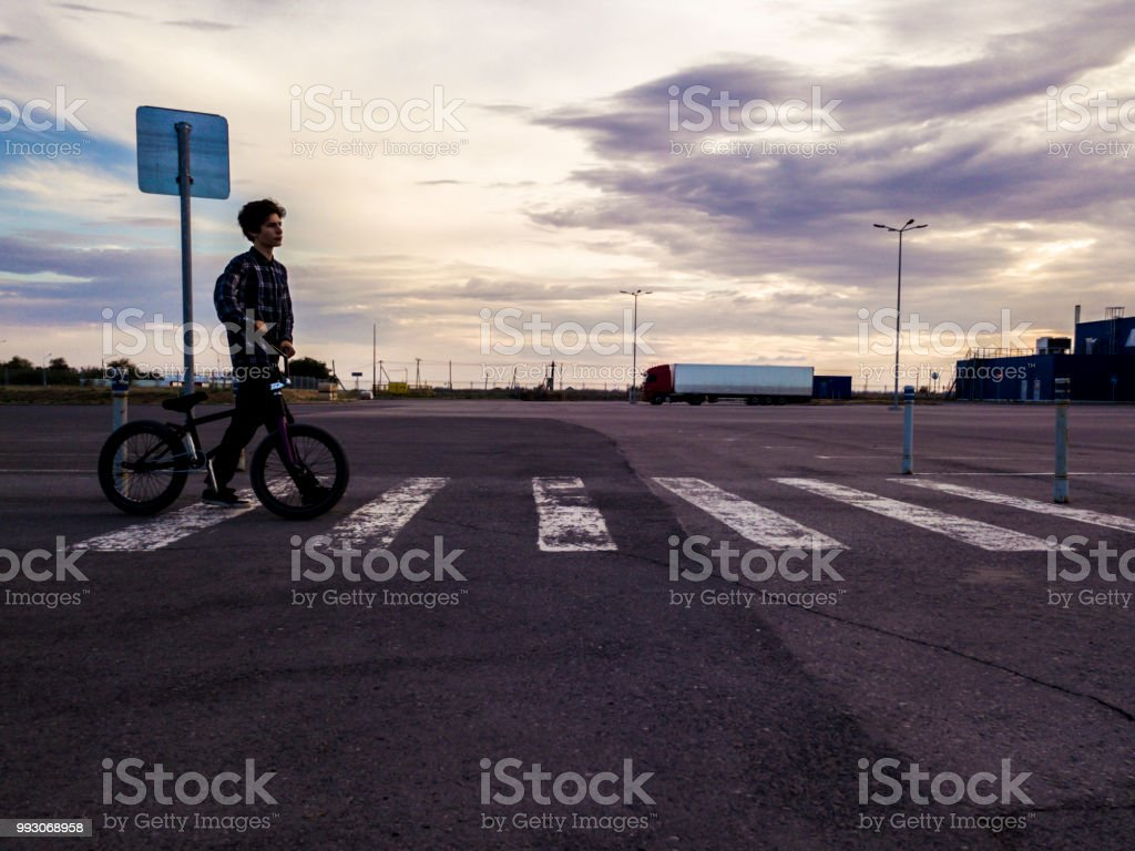 dark wide view of young rider cross the street with bmx bike stock photo