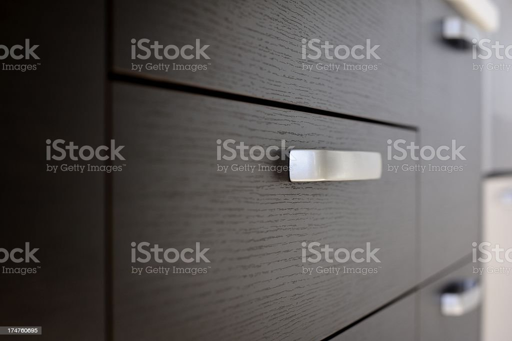 Dark wood kitchen drawers with silver handles stock photo